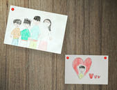 Drawing of family, paper on wood background — Stockfoto