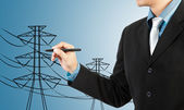 Business man drawing electric pylon and wire — Stock Photo
