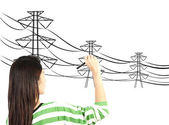 Woman drawing electric pylon and wire — Stock Photo