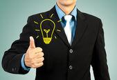 Empresário, dando-lhe o polegar para cima lâmpada conceito de idéia — Fotografia Stock