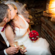 Stock Photo: Happy just married couple sitting in front of the fireplace