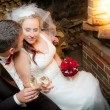 Young couple celebrating marriage in front of the fireplace — Stock Photo