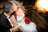 Happy just married couple sitting in front of the fireplace — Stock Photo
