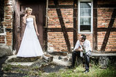 Young couple in front of the old house in the countryside — Stock Photo