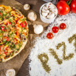 The words 'pizza' written on the flour with spices oregano — Stock Photo