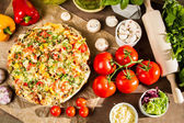 Baked pizza and ingredients — Stock Photo