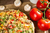 Close-up of pizzas and baked tomatoes — Stock Photo