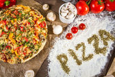 The words 'pizza' written on the flour with spices oregano — Fotografia Stock