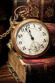 Alte taschenuhr und bücher in low-key — Stockfoto