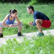Fit young couple stretching / warming up in a park. Selective fo — Stock Photo