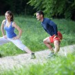 Cheerful fit young couple stretching / warming up in a park. Sel — Stock Photo