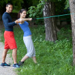 Stock Photo: Personal trainer working with his client. Resistance band exerci