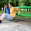 Happy young couple exercising outdoors, using a park bench to do - Zdjęcie stockowe