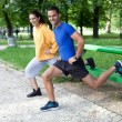 Happy young couple exercising outdoors, using a park bench to do - 
