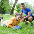 Stock Photo: Personal trainer working with his client, showing her how to pro