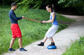 Personal trainer working with a young woman, balance exercise — Stock Photo