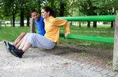 Casal jovem feliz exercitando ao ar livre, usando um banco de jardim para fazer — Foto Stock