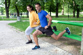 Happy young couple exercising outdoors, using a park bench to do — Φωτογραφία Αρχείου