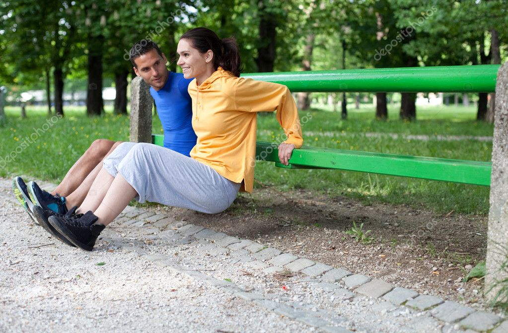 Happy young couple exercising outdoors, using a park bench to do a triceps exercise — Stock Photo #10777851