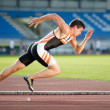 Foto de Stock  : Sprinter leaving starting blocks on running track. Explosive
