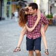 Young man giving piggyback ride to his girlfriend - Stock Photo