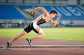 Sprinter dejando los podiums en la pista de atletismo. explosivo — Foto de Stock