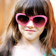 Close-up portrait of child girl in pink sunglasses — Stock Photo