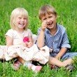 Portrait of cute kids sitting on green grass — Stock Photo