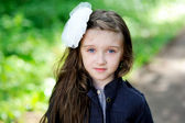 Cute little girl with white bow in her hair — Stock Photo