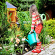 Little girl in a garden with green watering can — Stock Photo