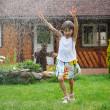liten flicka uppfriskande själv i en trädgård — Stockfoto