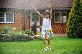 маленькая девочка, освежающий себя в саду — Стоковое фото
