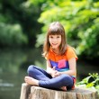 Little girl sitting on stump — Stock Photo