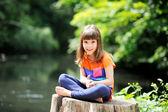 Little girl sitting on stump — Stock Photo