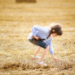Little girl picking up straws on field — Stock Photo