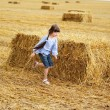 Little girl running around on a field — Stock Photo