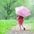 Kid girl walking outdoors with pink umbrella — Stock Photo