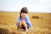 Uma menina sentada no topo de uma de palheiro — Fotografia Stock