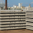 Pallets of new concrete blocks under sunlight against blue sky - Stock Photo