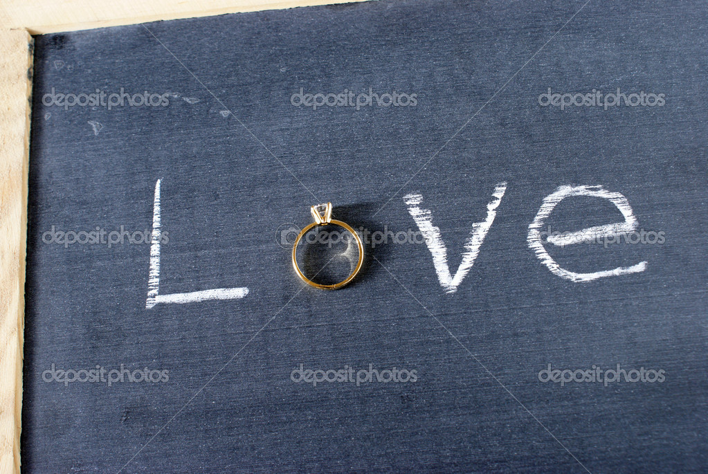The word love spelled out on a chalkboard with a letter replaced with a diamond ring.  Stock Photo #11034100
