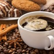 Coffee cup, sweets, cinnamon, anise on coffee beans - Stock Photo