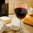 Stock Photo: Red wine, Brie, Camembert and bread on the table