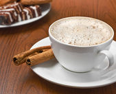 Cappuccino with cinnamon and sweets on the table — Stock Photo