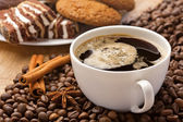 Coffee cup, sweets, cinnamon, anise on coffee beans — Stock Photo