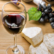 Red wine, Brie, Camembert and grape on the wood table — Stock Photo #10982344