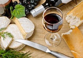 Red wine, Brie and Camembert cheeses with bread on the table — Photo