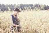 Girl in blue dress hug armful of wheat — Stock Photo
