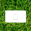 Energy concept light switch set in fresh spring green grass — Stock Photo