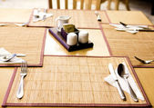 Table appointments- fork,knife,spoon, silk napkin on bamboo mat — 图库照片