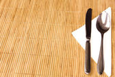 Table appointments- fork,knife,spoon, silk napkin on bamboo mat — Stock Photo